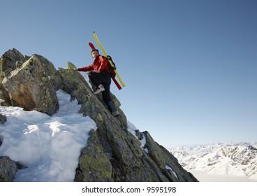 Male ski-climber climbing a rocky ridge; copy-space on the right. Italian alps.