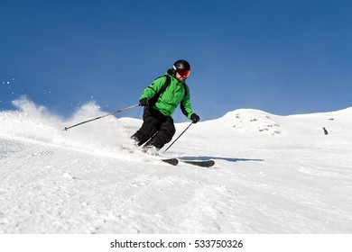 Male skier in green ski jacket skiing down ski slope on sunny day in the european alps.