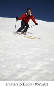 Male skier heading down the slope; blue sky on background; copy-space at the bottom