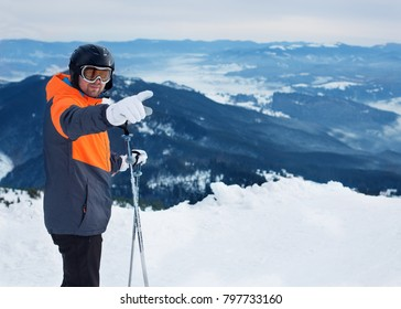 Male skier pointing at something while standing on top of mountain