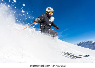 Male skier skiing in fresh snow on ski slope on a sunny winter day at the 55924acaf