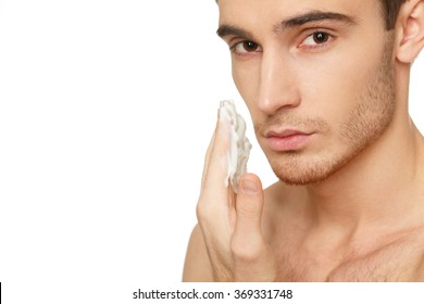 Male skin care. Studio shot of a handsome man applying shaving cream to his face copyspace on the side