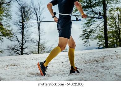 male skyrunner running mountain snowy trail with trekking poles