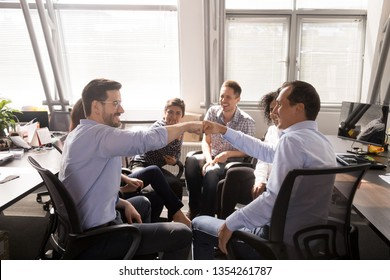 Male smiling colleagues fist bumping, celebrating successful teamwork, corporate success, business achievement at company meeting, business training, briefing, involved in team building activity