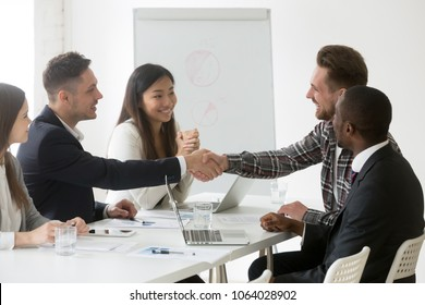 Male smiling partners shaking hands after signing contract at multiracial team business meeting, friendly businessman handshaking client satisfied with successful effective diverse group negotiation