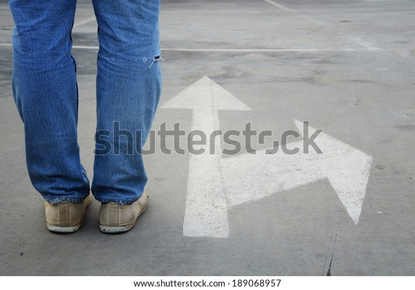 male sneakers with jeans on the tarmac road with white direction arrow, concept of making decision at the crossroad