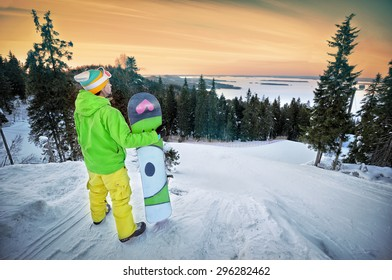 Male snowboarder against panoramic winter landscape background