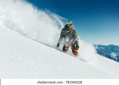 male snowboarder curved and brakes spraying loose deep snow on the freeride slope