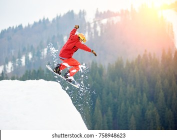 Male snowboarder freerider jumping from the top of the snowy hill with snowboard. Skiing and snowboarding concept