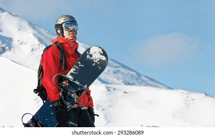 Male snowboarder holding a board with copy space
