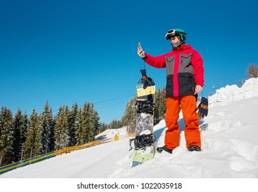Male snowboarder resting on the slope at ski resort, using his smart phone after snowboarding, taking photos of beautiful natural scenery copyspace technology connectivity mobility