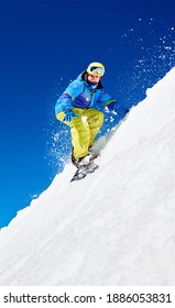 Male snowboarder riding snowboard fast down steep snowy mountain slope, jumping in air on copy space background of blue sky and white snow on sunny winter day. Extreme sport and recreation concept.