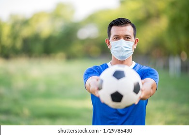 Male soccer football player Wear a mask when practicing soccer football on the lawn