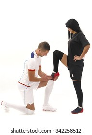 male soccer player cleaning female soccer player's shoe.  Man in white and woman in black;