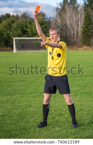 Male Soccer Referee Holding Up A Red Card During Football Game