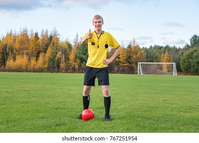Male soccer referee standing with a soccer ball in a soccer field.