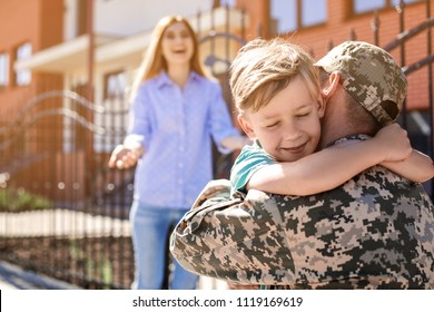 Male soldier hugging with his son outdoors. Military service