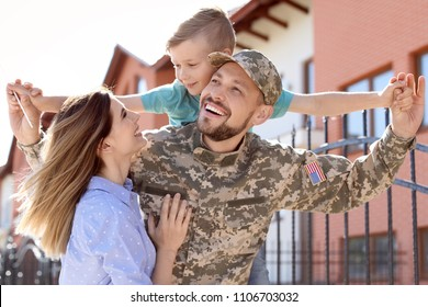 Male soldier reunited with his family outdoors. Military service