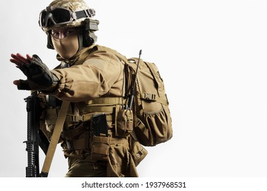 Male soldier in tactical equipment and uniform (coyote brown color) . Shot in studio on a white background