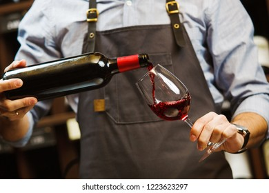 Male sommelier pouring red wine into long-stemmed wineglasses.
