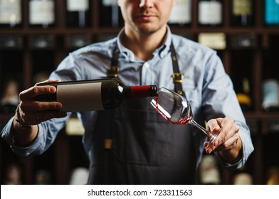 Male sommelier pouring red wine into long-stemmed wineglasses. Waiter with bottle of alcohol beverage. Bartender at bar counter pour elite drink into long-stemmed glass