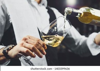 Male sommelier pouring white wine into wineglasses.