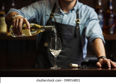 Male sommelier pouring white wine into long-stemmed wineglasses.