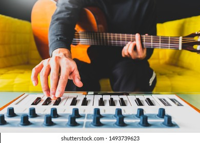 male songwriter playing guitar and keyboard for creating melody, harmony in a song. song writing concept