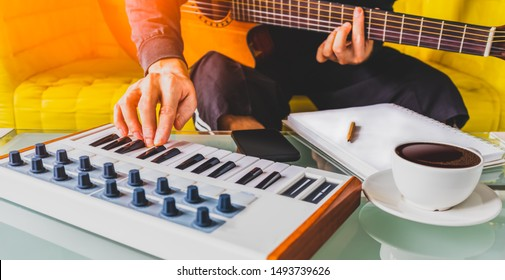 male songwriter playing guitar, keyboard and writing a song in living room. song writing concept