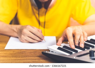 male songwriter playing keyboard and writing a song. song writing concept