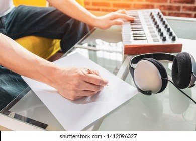 male songwriter playing music keyboard and writing a song on blank white paper, song writing concept