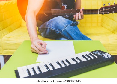 male songwriter writing a song with acoustic guitar & music keyboard in living room