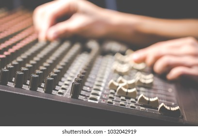 male sound engineer hands working on audio mixing console.