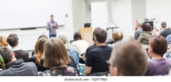 Male speaker giving presentation in lecture hall at university workshop. Audience in conference hall. Rear view of unrecognized participant in audience. Scientific conference event.