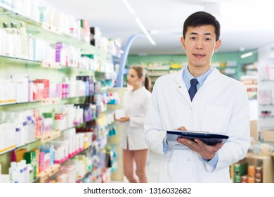 Male specialist is attentively stocktaking medicines with notebook near shelves in pharmacy