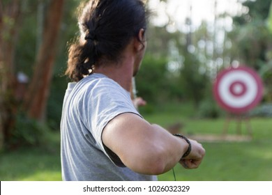 A male sport archer shooting an arrow with a bow at a red wooden target