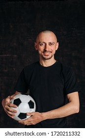 A male sports teacher stands against a dark background, holding a soccer ball