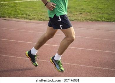 Male sprinter muscular strong legs, close up.
