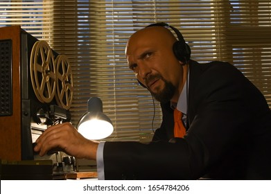 A male spy listens and records conversations on a reel-to-reel tape recorder, intelligence and spying on citizens, and a super-agent with headphones.