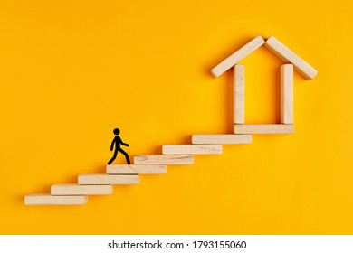 Male stickman climbing the ladders towards home formed by wooden blocks on yellow background.