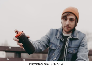 male street artist holding can with spray paint