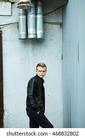 Male street fashion concept. Portrait of brutal young man with short hair wearing black leather jacket, posing over urban, industrial background. Outdoor shot