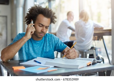 Male student with African hairstyle sitting at wooden desk talking on smart phone with his best friend, discussing latest news and looking seriously in textbook underline something with pencil