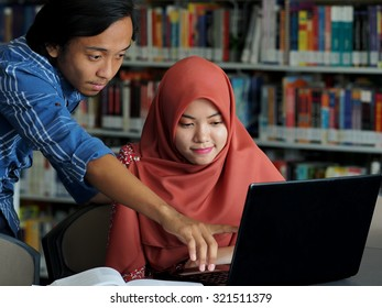 A male student assisting his friend in a library.