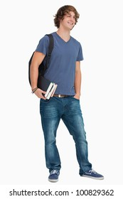 Male student with a backpack holding books against white background