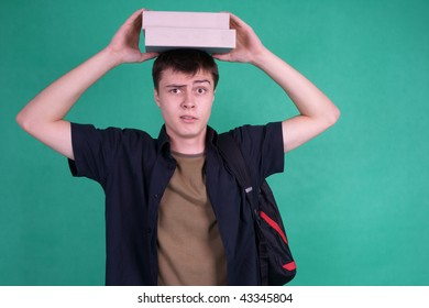 Male student balancing books on his head