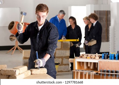 Male student with chisel learning bricklaying at technical college