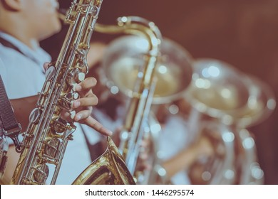 Male student with friends blow the saxophone with the band for performance on stage at night.