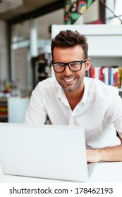 Male student with geek glasses in front of his laptop