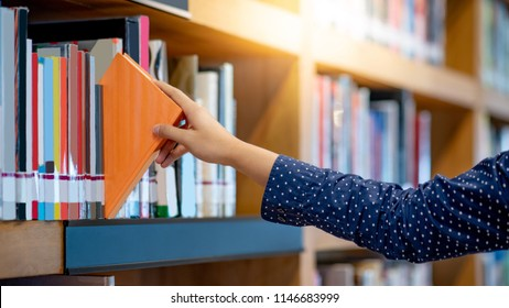 Male student hand choosing and picking off orange handcover book from bookshelf in college library for education research. Bestseller collection in bookstore. Scholarship and educational opportunity